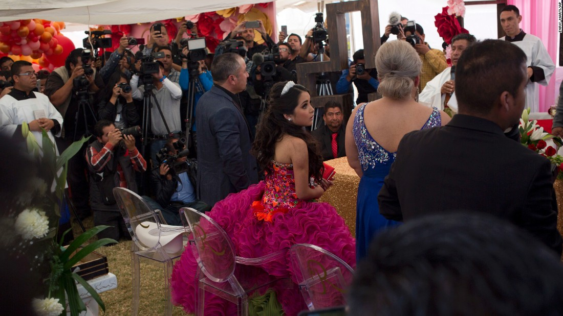 "Rubi Ibarra makes her way through the crowd to her birthday Mass at her Quinceanera party on Monday. Millions of people responded to the invitation in rural Mexico after her parent's video asking ""everybody"" to attend went viral."