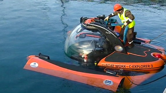 Emergency Ministry personnel prepare a submersible craft Tuesday to search for sunken wreckage and victims