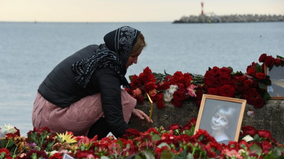 A woman lights a candle Tuesday next to makeshift memorial in Sochi, Russia, for  Russian activist Elizaveta Glinka, who was killed in the crash. Also presumed dead were nine journalists and more than 60 members of the Russian army