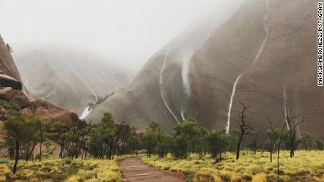 Water flows down the face of Uluru after a rare meteorological event at Uluru-Kata Tjuta National Park in Australia.