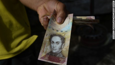 A man shows a 100-Bolivar note in a market at Petare shantytown in Caracas on December 19, 2016.    A jetload of new currency finally arrived in Venezuela on December 18 after its delayed arrival sparked protests and looting that jolted President Nicolas Maduro's unpopular government. / AFP / FEDERICO PARRA        (Photo credit should read FEDERICO PARRA/AFP/Getty Images)