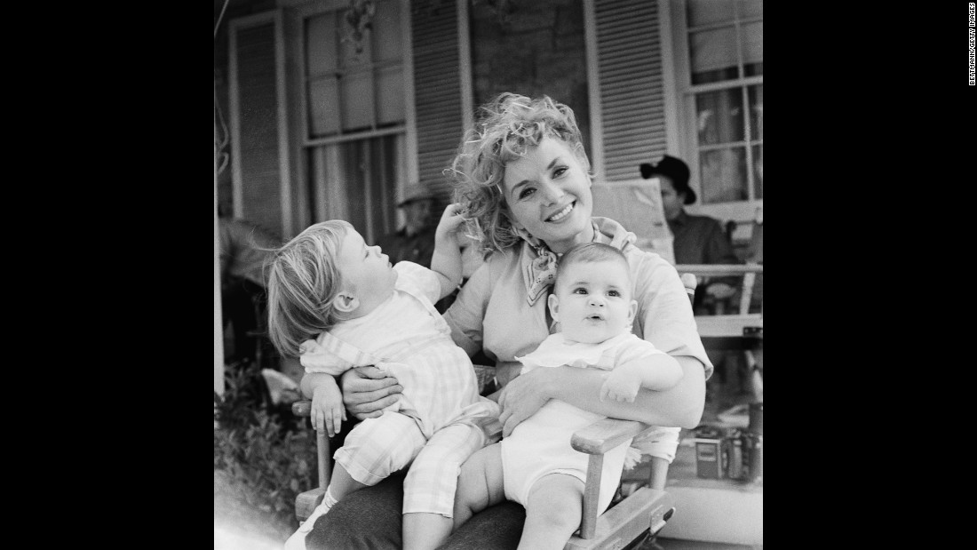"Reynolds holds her two children, Carrie and Todd, right, during the shooting of 1959's ""The Mating Game."""