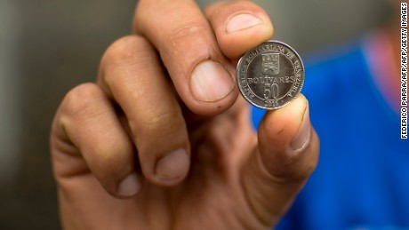 A man holds a new 50-Bolivar-coin at a kiosk in Caracas on December 28, 2016. Venezuela took delivery on December 27 of its third load of new, bigger denomination banknotes, its central bank said, but there was no sign of them in circulation yet despite official promises and mounting public anxiety. Maduro's announcement that the 100-bolivar notes would suddenly no longer be legal tender provoked long lines of people trying to change them, and looting and rioting in some areas, resulting in four deaths. / AFP / FEDERICO PARRA        (Photo credit should read FEDERICO PARRA/AFP/Getty Images)