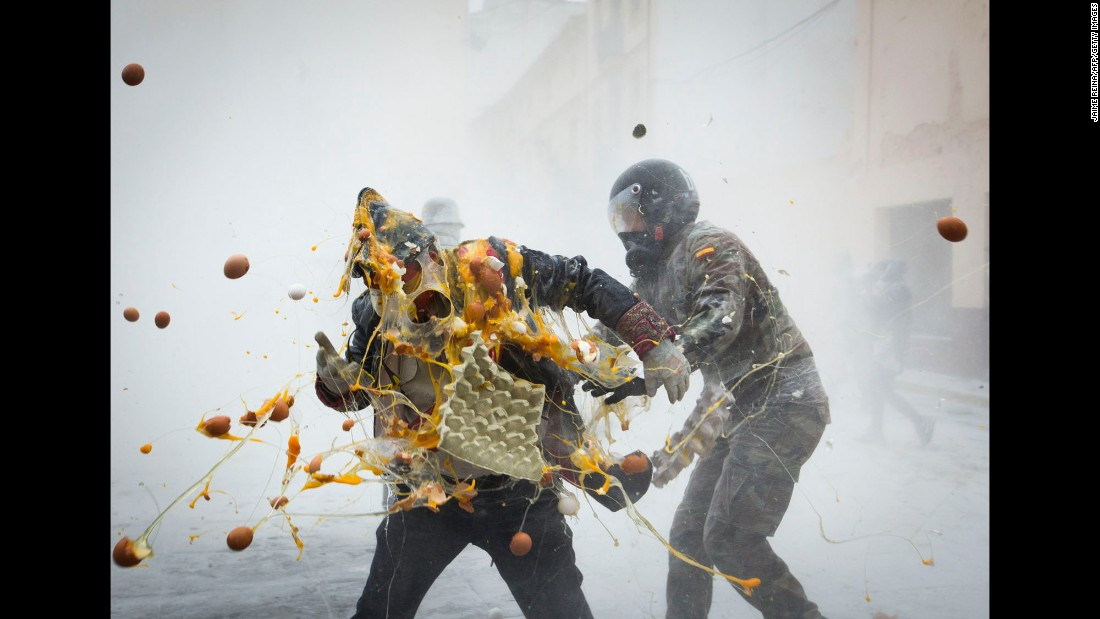 "Revelers dressed in mock military garb take part in an ""Enfarinats"" battle in the southeastern Spanish town of Ibi on Wednesday, December 28. During this 200-year-old traditional festival, participants known as ""Els Enfarinats"" dress in military clothes and stage a mock battle using flour, eggs and firecrackers. <br />"