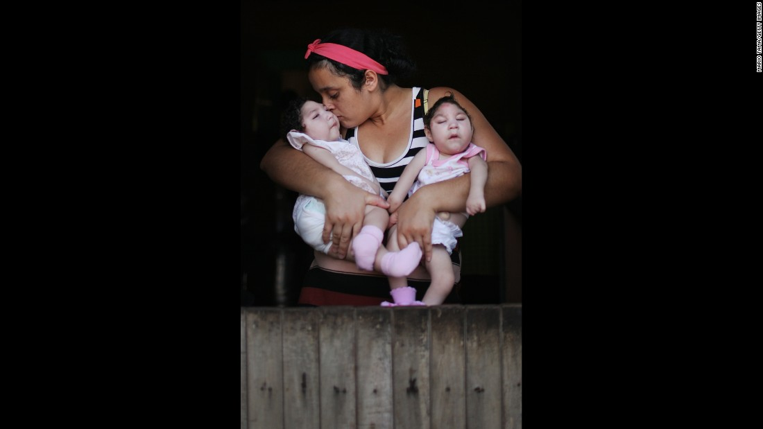 "Raquel Barbosa poses on Sunday, December 25 in Areia, Brazil holding her twin daughters Eloisa, left, and Eloa, both 8 months old and both born with microcephaly. Raquel said she <a href=""http://www.cnn.com/2016/11/18/health/who-ends-zika-public-health-emergency/"" target=""_blank"">contracted Zika</a> during her pregnancy.<br />"