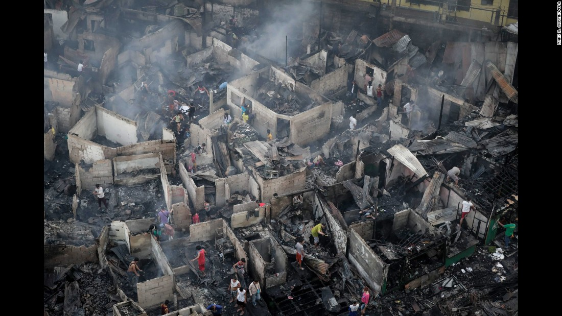 Filipino residents search for salvageable materials following a fire in Quezon City, northeast of Manila, Philippines, on Wednesday, December 28. <br />