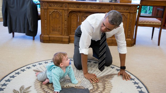 """""""The President is always asking staff to bring their babies and young kids by for a visit. Here, during a break between meetings one afternoon, the President crawled around in the Oval Office with Communications Director Jen Psaki's daughter Vivi."""" (Official White House Photo by Pete Souza)"""