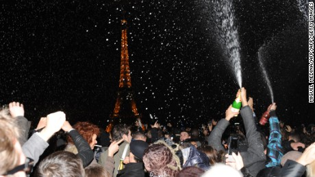 People spray champagne as they celebrate the New Year on the Trocadero square in front of the Eiffel Tower in Paris, early on January 1, 2012. AFP PHOTO / MIGUEL MEDINA (Photo credit should read MIGUEL MEDINA/AFP/Getty Images)