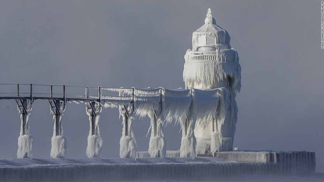 Ice covers the lighthouse and pier during extreme cold on the southeastern shoreline of Lake Michigan in St. Joseph, Michigan, on Monday, December 19.