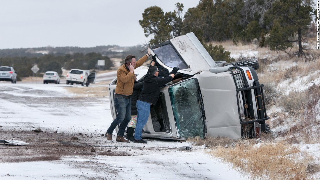 Motorists help a passenger and a driver escape an overturned vehicle on Interstate 25 north of Santa Fe, New Mexico, on Thursday, December 22.