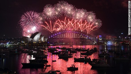 Fireworks illuminate the sky over the Opera House and Harbour Bridge in Sydney, Australia.