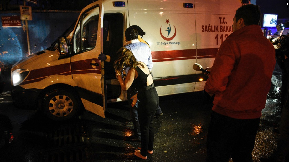 A wounded person is put into an ambulance.