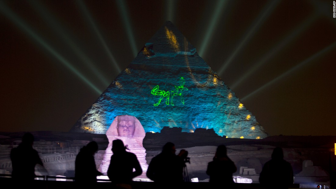 People watch a light show by the Giza Pyramids and Sphinx in Egypt.