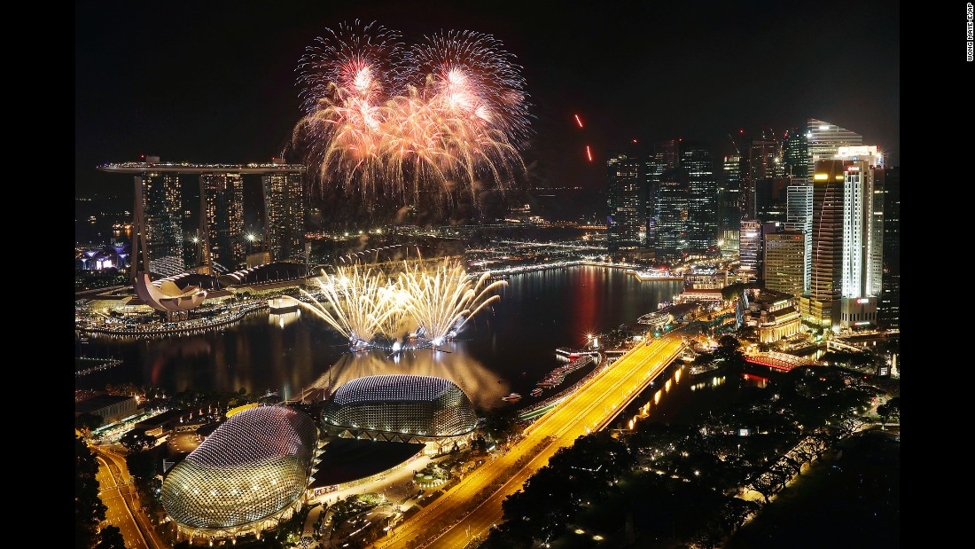 Fireworks explode above Singapore's financial district at the stroke of midnight.