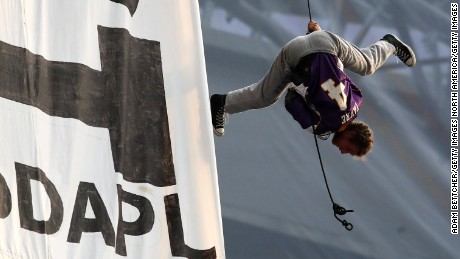 MINNEAPOLIS, MN - JANUARY 1: A protestor wearing a Brett Farve jersey dangles upside down above Minnesota Vikings and Chicago Bears football game on January 1, 2017 at US Bank Stadium in Minneapolis, Minnesota. Two protesters hung a banner in opposition to the Dakota Access Pipeline from the rafters of the stadium in the second quarter of the game. (Photo by Adam Bettcher/Getty Images)