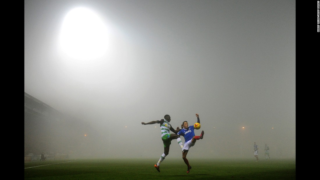 Players from Yeovil Town and Portsmouth compete for a ball during a foggy soccer match in Yeovil, England, on Friday, December 30. The two clubs play in League Two, which is the fourth tier of pro soccer in England.