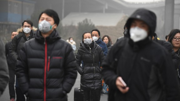 Commuters wear masks on a polluted day in Beijing on December 20, 2016. 