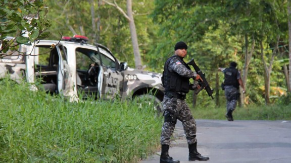 Military police officers track possible fugitives of the Anisio Jobim Penitentiary Complex after a 17-hour riot broke out Sunday.