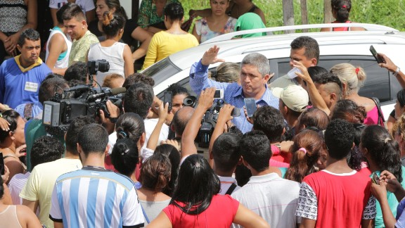 An unidentified man speaks to relatives of inmates and to the media near the main gate prison complex.