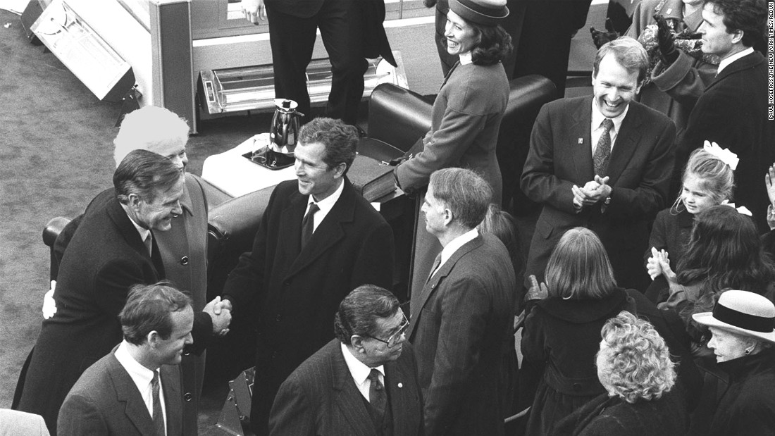 President George H.W. Bush, left, shakes the hand of his son George W. Bush after being sworn in to office in 1989. The elder Bush had been vice president under President Ronald Reagan, whose two terms were up.