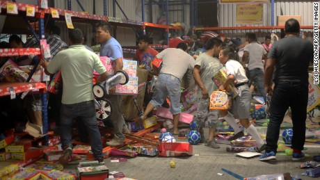 People pick up toys as they loot a store during a protest in the port city of Veracruz, Mexico, on Wednesday.