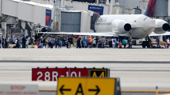 People stand on the tarmac at the Fort Lauderdale-Hollywood International Airport after a shooter opened fire inside the terminal, killing several people and wounding others before being taken into custody, Friday, January 6 in Fort Lauderdale, Florida.