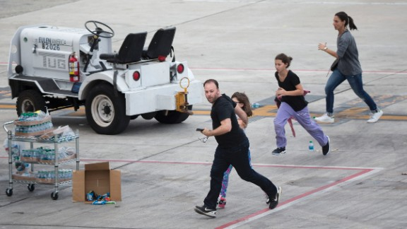 People run out on the tarmac in the aftermath of the shooting Friday, January 6, at the airport in Fort Lauderdale, Florida. Five people were killed and eight others were wounded, officials said.