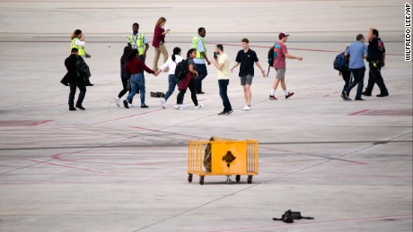People are shown on the tarmac at Fort Lauderdale--Hollywood International Airport, Friday, January 6, in Fort Lauderdale, Florida. A gunman opened fire in the baggage claim area at the airport Friday, killing several people and wounding othersbefore being taken into custody in an attack that sent panicked passengers running out of the terminal and onto the tarmac, authorities said.