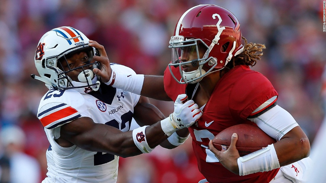 Alabama quarterback Jalen Hurts, right, tries to break a tackle by Auburn defensive back