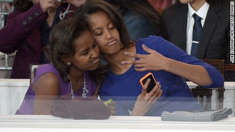 Sasha and Malia Obama, daughters of US President Barack Obama, take a photo of themselves during the Presidential Inaugural Parade on January 21, 2013 in Washington, DC.