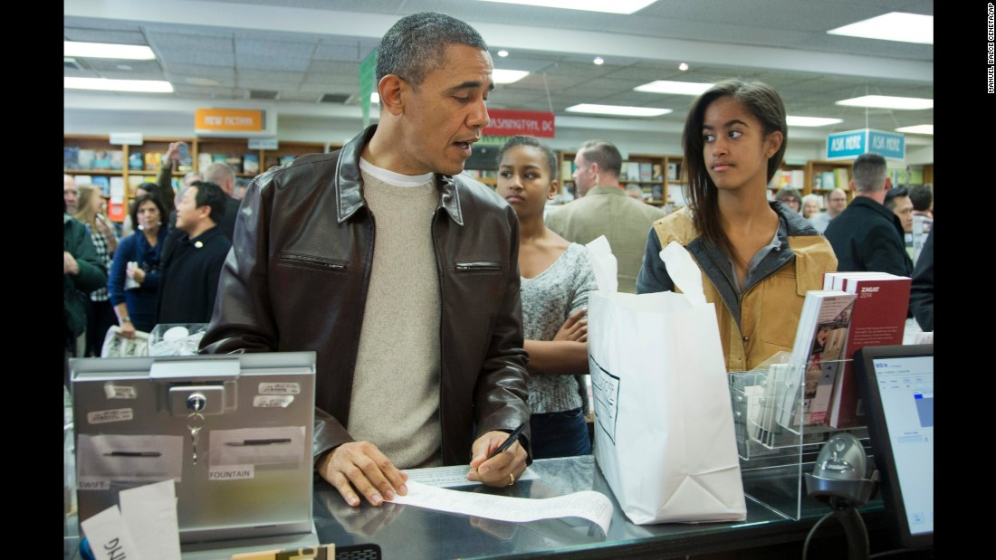 Obama, with Sasha, center, and Malia, pays for a purchase at the Politics & Prose bookstore in northwest Washington in November 2013.