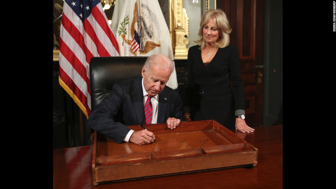 "Vice President Joe Biden signs the drawer of the vice president's desk as part of <a href=""http://www.cnn.com/2017/01/06/politics/joe-biden-desk-drawer/"" target=""_blank"">a farewell tradition</a> in the vice president's ceremonial office at the Eisenhower Executive Office Building in Washington, on Friday, January 6, as his wife Jill Biden watches."