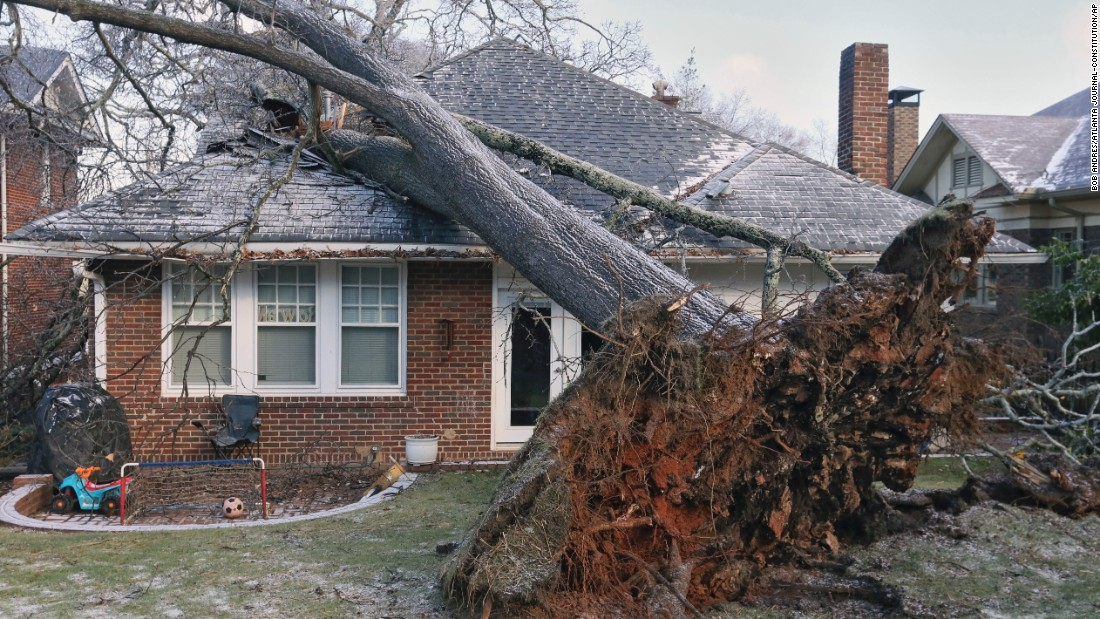 A tree fell on this Atlanta house early Saturday, January 7, trapping a child, who was rescued through a window. No one was injured. The storm knocked out power to more than 10,000 customers across metro Atlanta by early Saturday, Georgia Power said.