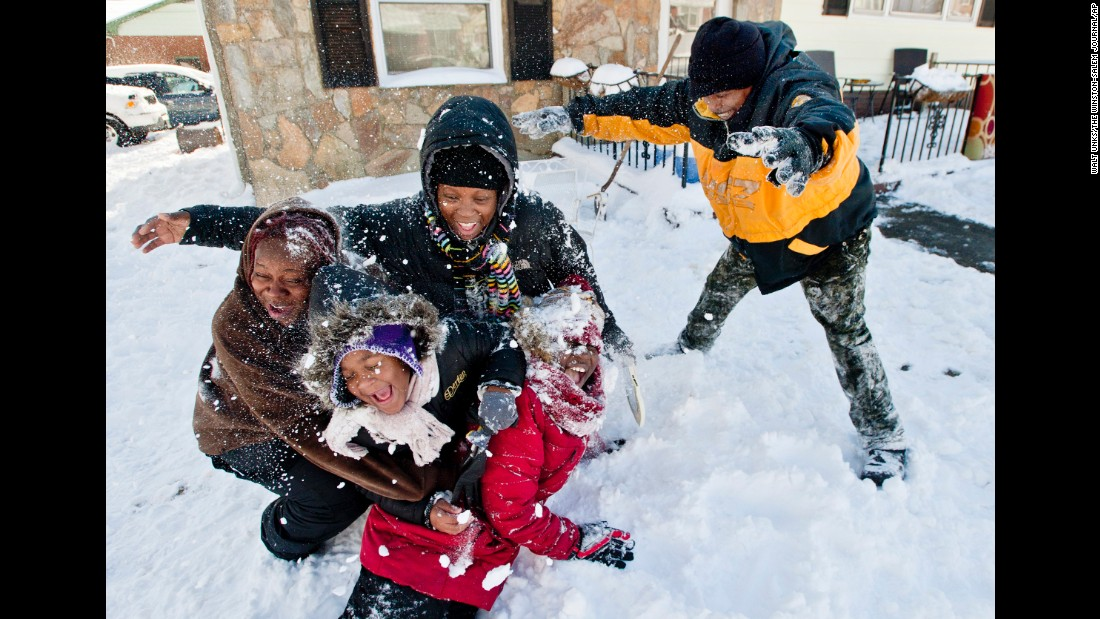 Barry Boykin throws snow on his neighbors Larniece Clemmons, Taylor Porter, Shondell Porter and Jaynea Smith, as they play  Saturday, January 7 in Winston-Salem, North Carolina.