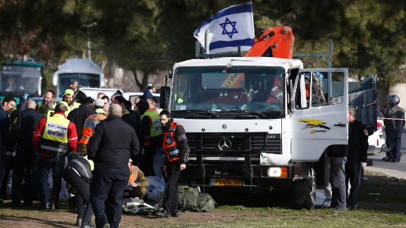"""Israeli security forces and emergency personnel gather at the site of a vehicle-ramming attack in Jerusalem on January 8, 2017. A truck ploughed into a group of soldiers in Jerusalem in what police said was a """"possible terrorist attack"""" in which at least four were killed and a number of people injured."""