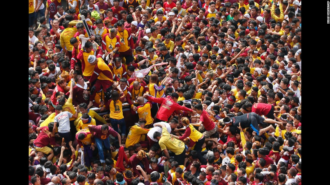 Devotees climb the carriage to kiss and rub the Black Nazarene.