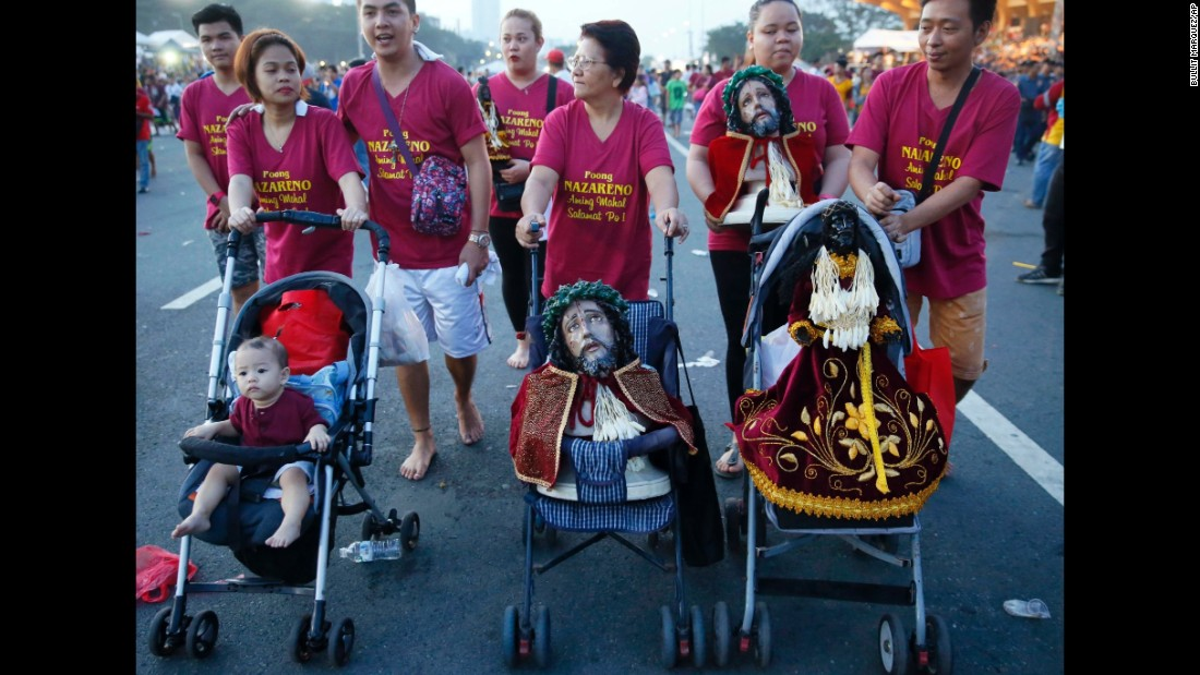 A family uses baby strollers to carry replicas of the image of the Black Nazarene on January 9.