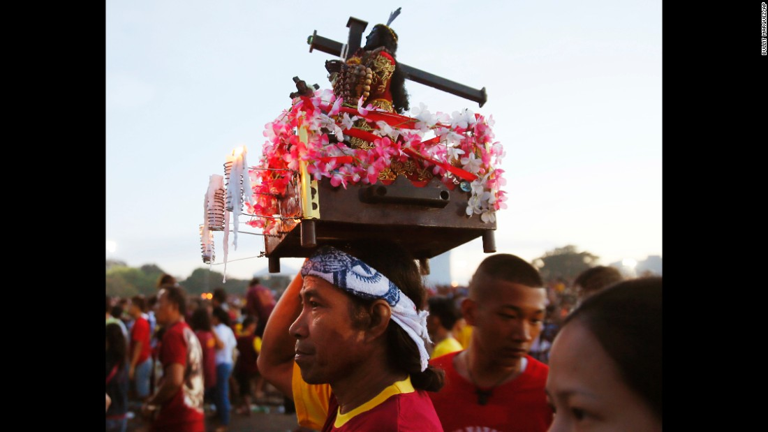 A devotee carries a replica of the Black Nazarene. The raucous celebration drew tens of thousands of devotees in a barefoot procession for several hours around Manila streets.