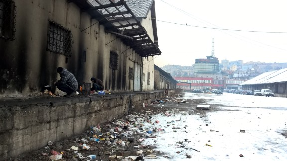 Asylum seekers light fires to keep warm at an abandoned warehouse in Belgrade.