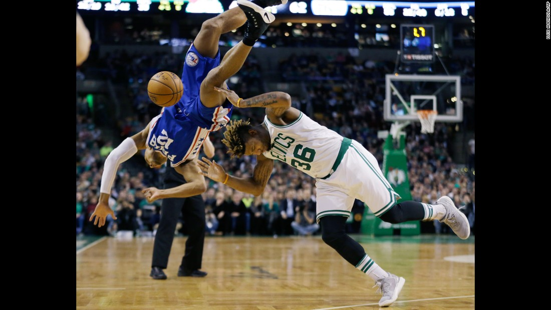 Philadelphia's Gerald Henderson, left, falls over Boston's Marcus Smart while trying to block a shot on Friday, January 6.