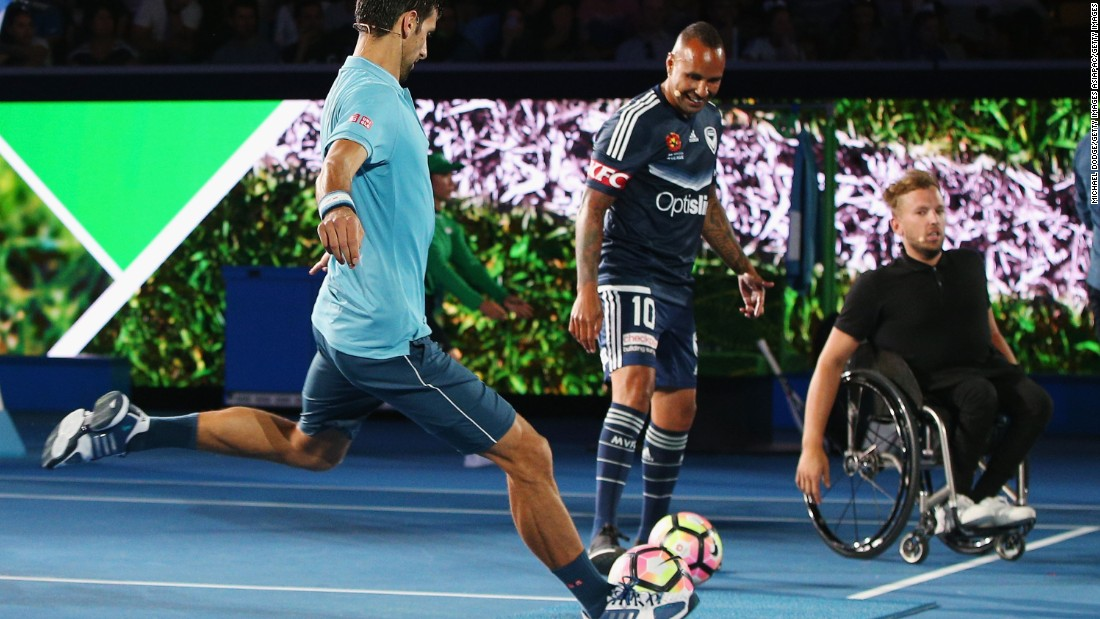 The tennis star has a go at football with Australian legend Archie Thompson (center) looking on. Thompson earned over 50 caps for Australia.