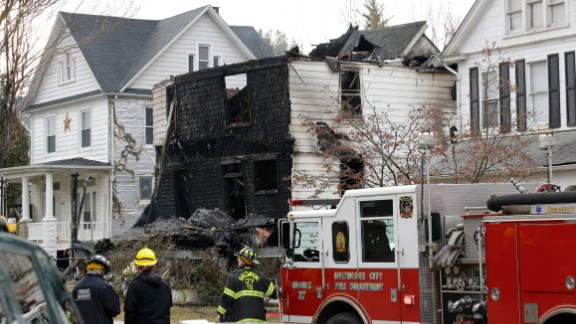 Fire officials stand at the scene of an early morning house fire in Baltimore, Thursday, Jan. 12, 2017. A woman and several children in the house were injured and multiple other children in the family are unaccounted for, a fire official said Thursday.