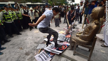"A protester tramples photos of Japanese Shinzo Abe in front of a state memorializing Korean WWII sex slaves, also known as ""comfort women."""