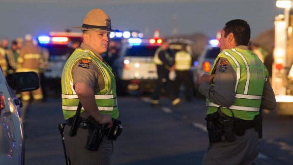 Emergency personnel gather at the scene where an Arizona Department of Public Safety trooper was shot, Thursday, Jan. 12, 2017, at the scene of a rollover accident on Interstate 10 near Tonopah, Ariz. An Arizona state trooper stopped to help at a car wreck along the remote highway Thursday when he was shot and wounded in an ambush by a man who was bashing the officer