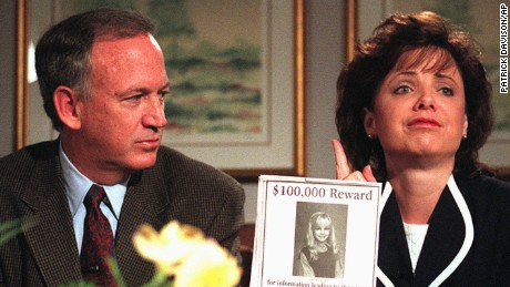 John Ramsey looks on as his wife, Patsy, holds an advertisement promising a reward for information leading to the arrest and conviction of the murderer of their 6-year-old daughter, JonBenet, during an interview Thursday, May 1, 1997, in Boulder, Colo. It was the Ramsey's first meeting with reporters since the days after their daughter was found slain in the basement of their family's home in Boulder, Colo., on Dec. 26, 1996.  No arrests have been made in the girl's death. (AP Photo/Rocky Mountain News, Patrick Davison)   PLEASE CREDIT: Patrick Davidson, Rocky Mountain News