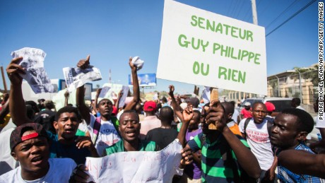 "Supporters of elected Haitian elected senator Guy Philippe protest holding a sign that translates ""Senator Guy or nothing"" in front of the US embassy on January 13, 2017 in Tabarre a commune of Port-au-Prince.  The protesters demanded the unconditional return of Phillippe who was arrested on January 5, 2017 by the national police of Haiti and extradited to the United States under escort of the DEA.  / AFP PHOTO / Pierre Michel JeanPIERRE MICHEL JEAN/AFP/Getty Images"