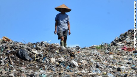 An Indonesia scavenger walk on a garbage dump in Denpasar on the island of Bali on January 28, 2013. AFP PHOTO/Sonny TUMBELAKA        (Photo credit should read SONNY TUMBELAKA/AFP/Getty Images)