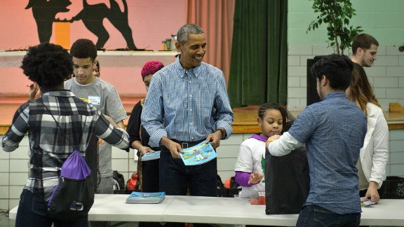 President Barack Obama helps give out books at Leckie Elementary School while celebrating Martin Luther King Day January 18, 2016 in Washington, DC.