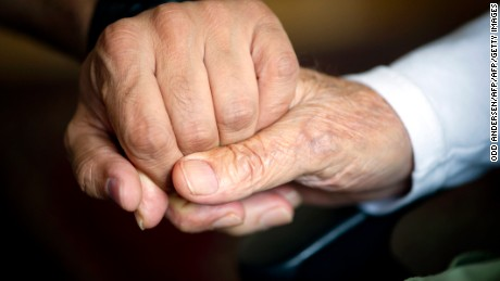 92 year old Ali Haydar Cilasun (R) holds the hand of carer Guven Asmacik (L) in his room at an Aliacare home for the elderly in Berlin on October 8, 2013. The Aliacare home offers bilingual services for German and Turkish elderly people. AFP PHOTO / ODD ANDERSEN        (Photo credit should read ODD ANDERSEN/AFP/Getty Images)