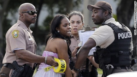 A concerned mother is meet by Miami-Dade police officers as she searches for her child after several were injured in a shooting at Martin Luther King Jr. Memorial Park in Miami-Dade, Fla., Monday, Jan. 16, 2017. The Miami Herald reports that hundreds of people had gathered in the park after the annual MLK Day parade. (Carl Juste/Miami Herald via AP)